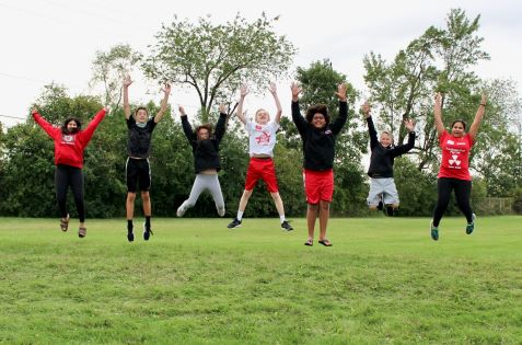 Robotics team jumping in the air
